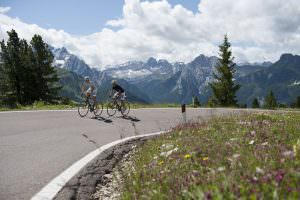 Cycling up the Swiss mountains with snow capped mountains in the background